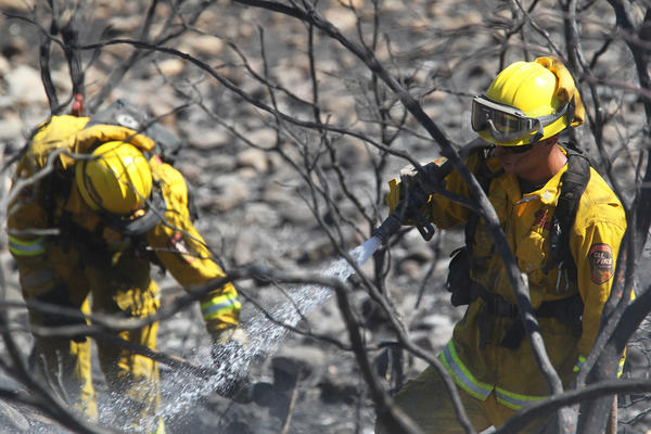 Firefighters mop up along Lower Gas Point Road after the Clover fire in Shasta County.