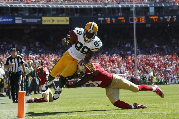 The 49ers' Donte Whitner couldn't stop Packers tight end Jermichael Finley as Finley leaps for a touchdown.