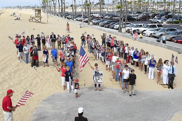 Dozens participate in forming a 9/11 shape while holding American flags during an event Wednesday next to the Balboa Pier.