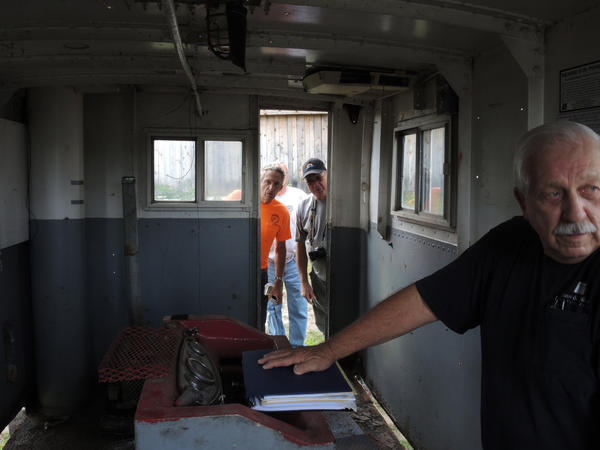 Members of the Northern Michigan Antique Flywheelers inspect the interior of the donated cab of the Ironton Ferry. In the foreground is Fred Hamilton, Norwood Township supervisor and member of the Charlevoix County Transportation Authority, which oversaw the ferry's overhaul.