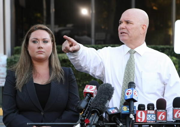 Attorney Kelly Sims points as client Shellie Zimmerman watches at a news conference on Wednesday.