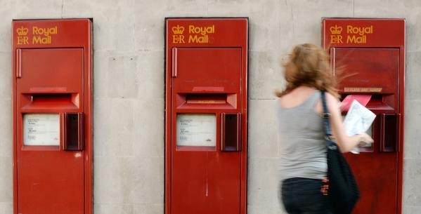 A woman posts her mail at a Royal Mail post box in central London. The Conservative-led government hopes to privatize the the Royal Mail, but drew immediate criticism from the Labor Party and unions.