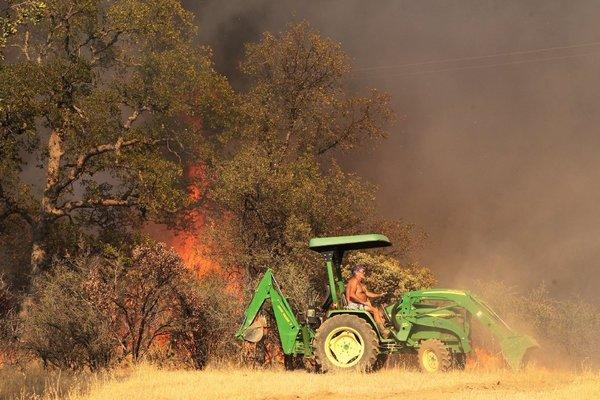 Dennis Martineau tries to protect his home off Gas Point Road in Anderson, Calif., on Monday.