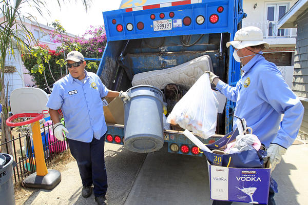 Newport Beach city trash collectors David Guzman, left, and Art Mitchell collect trash in a back alleyway, between Montero Avenue and Anade Avenue, in Newport Beach on Monday.
