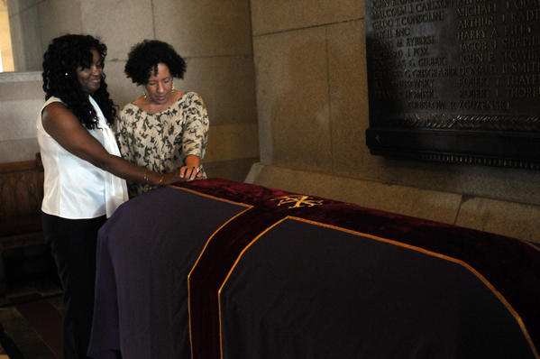 Tamara Lanier of Norwich, left and Gabrielle Foreman of Delaware say a prayer over the casket of the former slave Fortune lying in repose beneath the rotunda of the state Capitol Thursday. Fortune died in 1798.