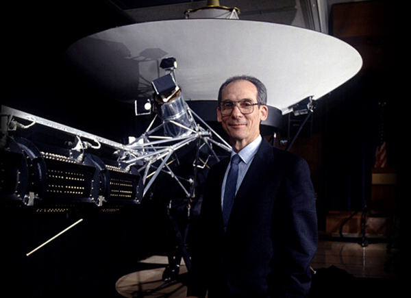 Ed Stone, Voyager project scientist at Caltech, stands before a model of the spacecraft.