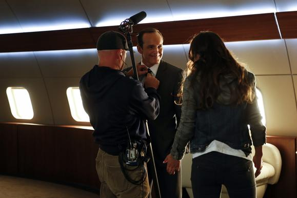 Before a scene is shot, Clark Gregg's mic is adjusted as he talks to Chloe Bennet.