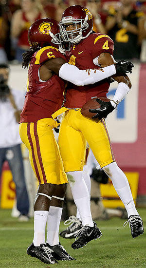 USC cornerback Torin Harris is congratulated by teammate Josh Shaw after intercepting a pass by Washington State quarternback Connor Halliday on Saturday.