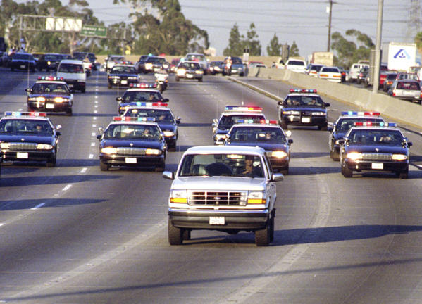 California Highway Patrol officers chase Al Cowlings, driving, and O.J. Simpson, hiding in the rear of a white Ford Bronco, on the 91 Freeway.