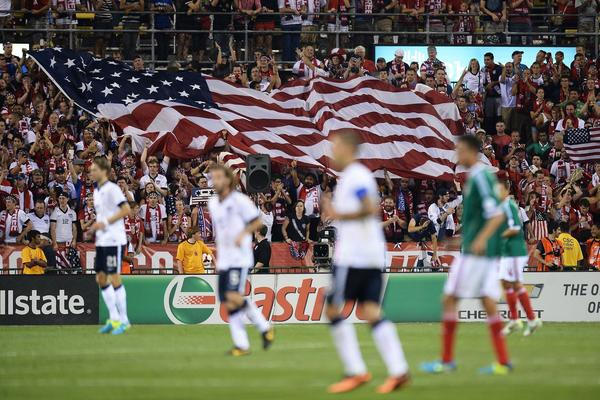 Fans unfurl a large U.S. flag after the U.S. men's national team scored their second goal against Mexico on Saturday.