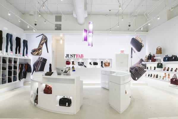 Handbags, shoes and jeans are on display in the bright new JustFab flagship store at the Glendale Galleria.