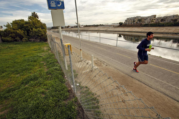 A jogger uses a path that runs along Ballona Creek near where the Annenberg Foundation plans to build an interpretive center.