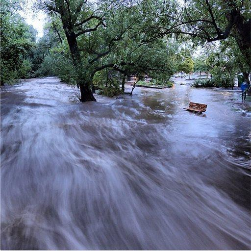 Flood waters course through a small park in Boulder, Colo., in this image made with a slow shutter speed.