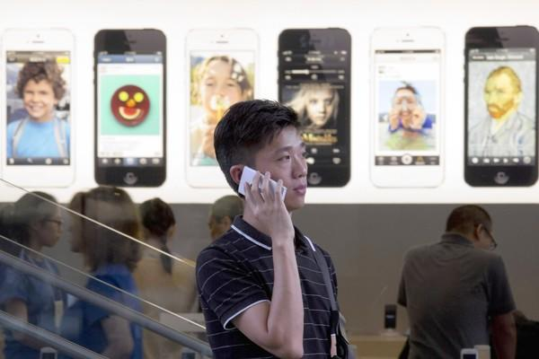 Apple has been losing market share to rivals such as Samsung Electronics Co., with its Android-based phones, and local competitors. For many in China, Apple's latest product launch brought a series of disappointments. Above, a man uses a non-Apple branded phone outside a Beijing store with iPhone ads.