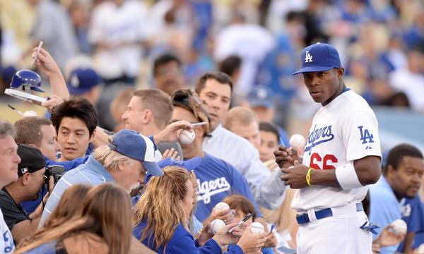 Dodgers right fielder Yasiel Puig signs autographs for fans before a game against the San Diego Padres in June.