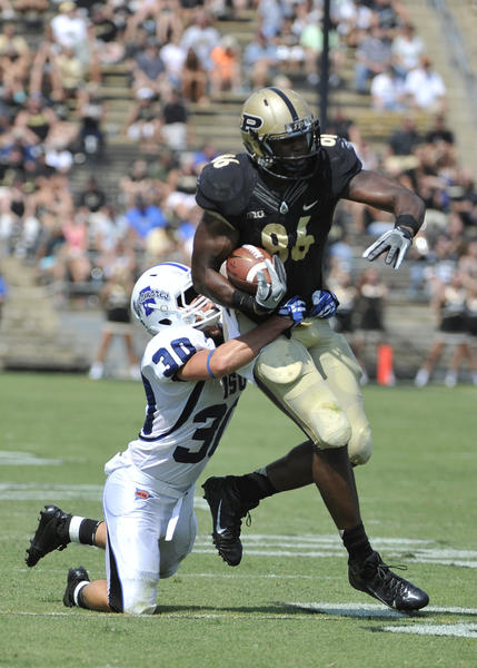 Purdue's Gabe Holmes runs after a catch with Indiana State's Tsali Lough hanging on in the 2nd half.