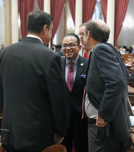 Assemblyman Luis Alejo, D-Watsonville, smiles as he talks with Sen. Joel Anderson, R-Alpine, left, and Mark Wyland, R-Escondido, as the Senate voted on Alejo's minimum wage bill Thursday.