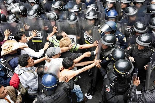 Striking teachers intending to block a main avenue try to push past a wall of riot police this week in Mexico City.