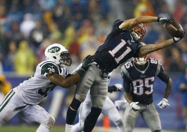 Julian Edelman of the Patriots catches a pass in front of the Jets' Antonio Allen #in the fourth quarter Thursday night in Foxborough, Mass. Edelman had 13 catches.