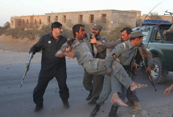 Afghan security personnel aid an injured police officer after militants attacked the U.S. Consulate in Herat, Afghanistan, early Friday.
