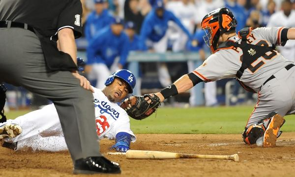 Dodgers left fielder Carl Crawford, left, slides safely into home plate past the tag of San Francisco Giants catcher Buster Posey for the game-ending run in the 10th inning of the Dodgers' 3-2 win Thursday.