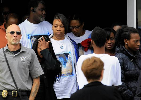 Brenda Lloyd, center, leaves the funeral of her 22-month-old grandson, Bryeon Hunter, at New Beginnings Church in Chicago. Robert Larson of K-9 Specialties, left, found the boy's body in the Des Plaines River. Bryeon's mother and her boyfriend are charged with his murder.