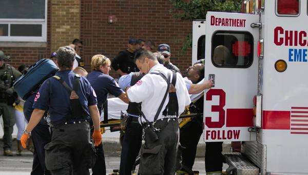 Chicago Fire Department Paramedics load a man into an ambulance following a standoff in the 1200 block of west Morse Avenue.