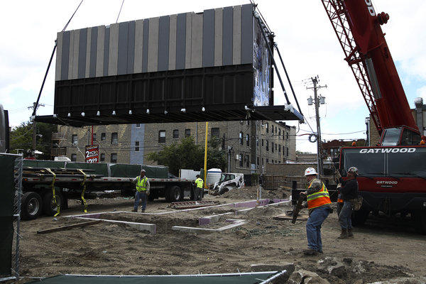 Workers move a piece of a new Starbucks with a crane at the corner of North Broadway and West Devon Avenue.