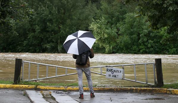 Grant Blakeman of Boulder, Colo. looks at a flooded field at Boulder High School Friday.