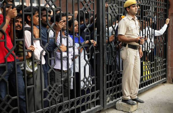 Indians behind the gates of a court complex in New Delhi watch protesters outside who were demanding that the juvenile involved in a December gang rape and murder also receive the death penalty.