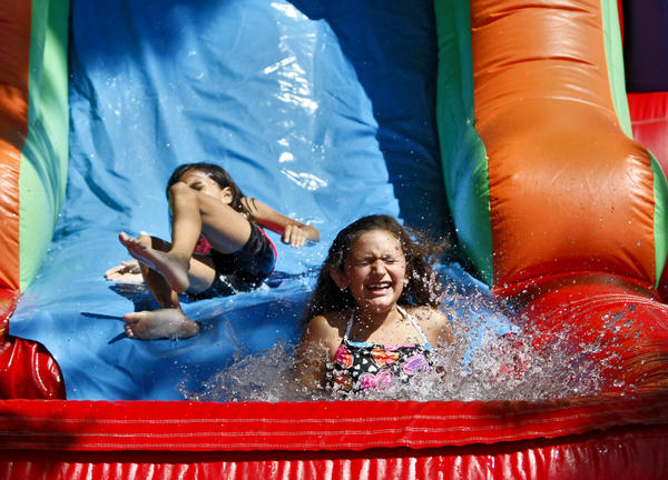 Fourth grader Sophia Martinez splashes into a pool of water after sliding down a water jumper during the Fabulous First Friday at First Lutheran School in Glendale on Friday, Sept. 13, 2013. The event is done on the first full week of school.