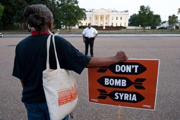 An anti-war demonstrator is seen outside the White House before President Obama addressed the nation on Syria Tuesday.