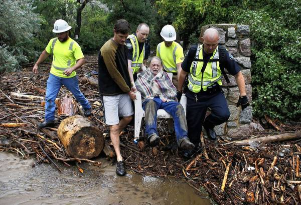 Emergency workers rescue Will Pitner, center, and neighbor Jeff Writer, left, after they were trapped on high ground at the base of Boulder Canyon in Colorado.