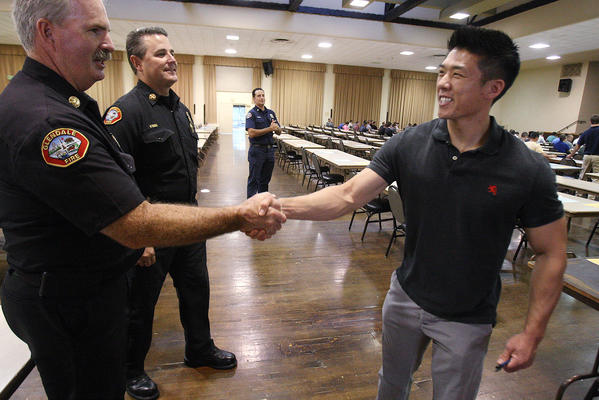 Stanley Woo, of Glendale, shakes hands with Battalion Chief Tom Propst and Battalion Chief Greg Fish as he enters the hall at the Glendale Civic Auditorium for a fire fighters examination on Tuesday, September 10, 2013. A couple hundred hopeful citizens, of over 1,800, took an exam as the first step to become one of 15 available positions in the Glendale Fire Department. This is Woo's first attempt at the test.