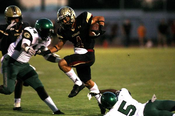 Brandon Pierce attempts to go between defenders Kristian Hanley and Aaron Corbin during Alemany's victory over Narbonne, 42-14, on Friday.
