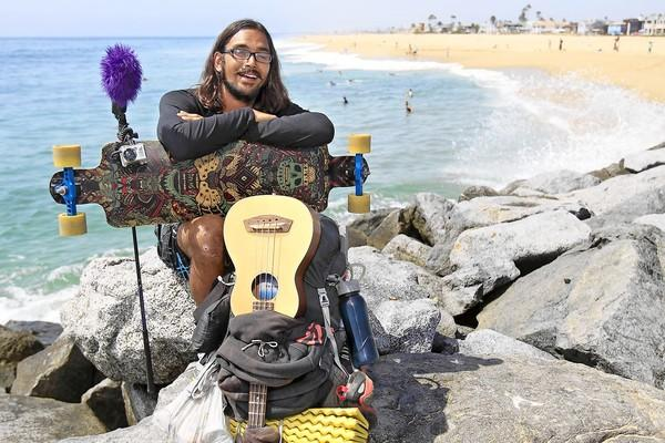 Darrian Balongie, 24, of Memphis, poses for a portrait with is belongings at the Wedge in Newport Beach on Friday. Balongie is longboarding from New York to San Diego to help raise money for St. Jude Children's Research Hospital in Memphis Balongie has about 90 more miles to go.