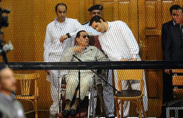 Former Egyptian Pesident Hosni Mubarak and his two sons Alaa, right, and Gamal stand behind bars during their trial in Cairo.