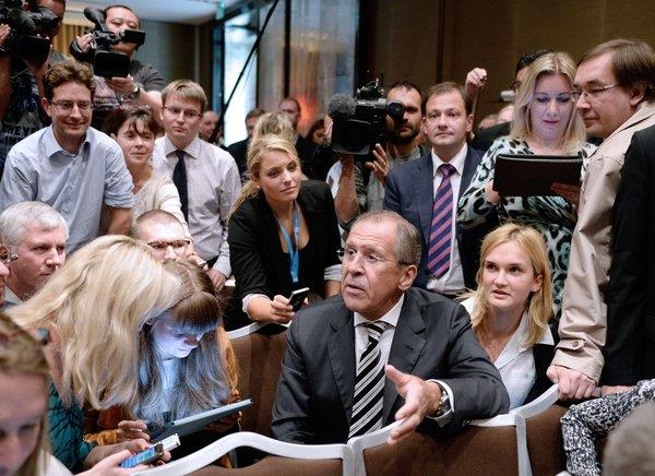 Russian Foreign Minister Sergey Lavrov, center, meets with journalists Saturday before briefing the press with his U.S. counterpart about the agreement they had reached on Syria's chemical weapons, which British and French officials have praised.