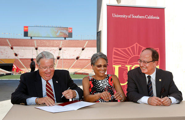 From left, Los Angeles County Supervisor Don Knabe, the president of the Coliseum Commission; Fabian Wesson, chair of the California Science Center board of directors; and USC President C.L. Max Nikias are all smiles as Knabe adds his signature during a ceremonial signing for USC's new lease agreement for operation of the Los Angeles Memorial Coliseum, seen in the background.
