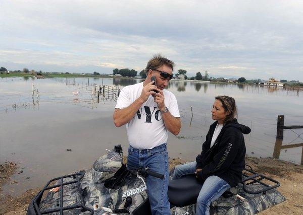 John Vogl talks on the phone while surveying floodwaters with his wife, Miracle, near Firestone, Colo.