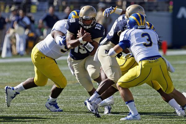 Navy quarterback Keenan Reynolds (19) runs through the middle of Delaware's defense