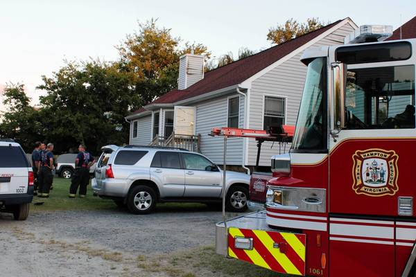 Hampton firefighters stand in front of a home in the 100 block of Bonita Drive in Hampton after extinguishing a fire that displaced three people.