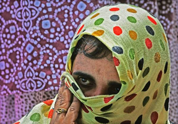An Indian sex worker belonging to the LGBT and HIV positive community listens to a speech during a protest against harassment last month in Bangalore.