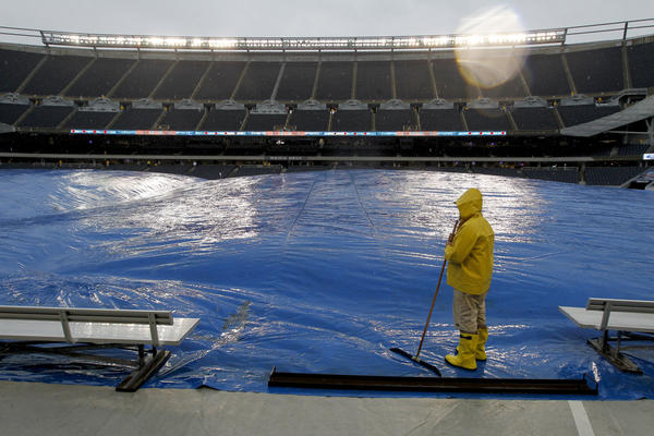 A grounds crew member waits on the tarp protecting the field as a steady rain falls before a game between the Chicago Bears and Minnesota Vikings at Soldier Field on Sunday.