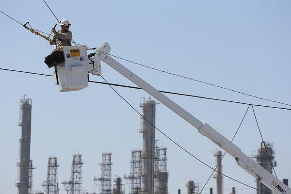 Gary Hatfield of Southern California Edison works on a damaged power line on 190th Street in Torrance. Tens of thousands of customers were affected by a power outage.