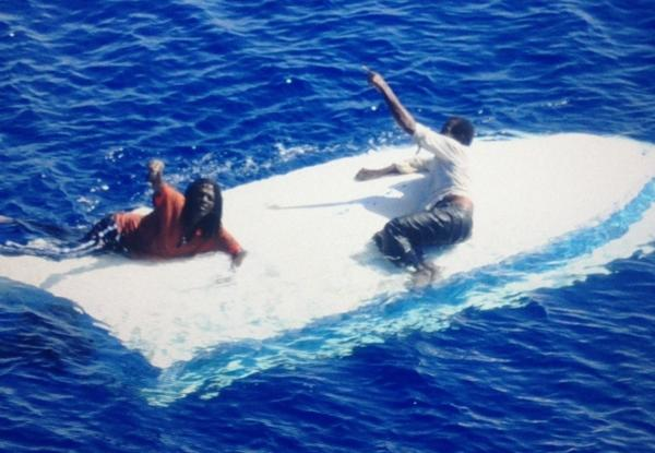 Two men cling to the hull of their capsized vessel shortly before being rescued by a U.S. Coast Guard helicopter Saturday east of Riviera Beach, Fla.