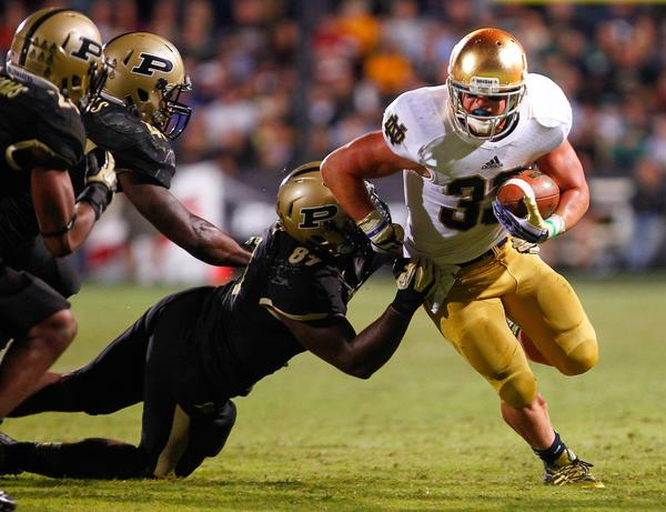 Cam McDaniel runs past Purdue's Jalani Phillips.