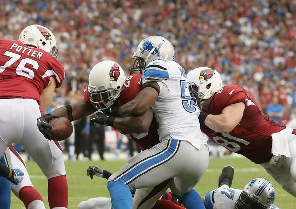 Rashard Mendenhall of the Cardinals stretches across the goal line for a touchdown while being tackled by linebacker Rocky McIntosh of the Lions in the fourth quarter.