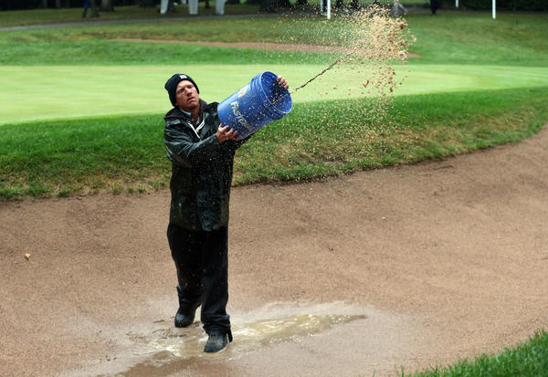 Volunteer Ben Pfeffer removes water from the bunker on the 1st hole during the rain delay.
