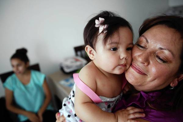 Susana Garcia snuggles with her granddaughter Phia Garcia, 9 months, with her daughter Cathya Garcia at left. With earnings of less than $13 an hour, she sees herself as part of the lower class.